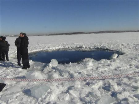 Russian police work near an ice hole, said by the Interior Ministry department for Chelyabinsk region to be the point of impact of a meteorite seen earlier in the Urals region, at lake Chebarkul some 80 kilometers (50 miles) west of Chelyabinsk February 15, 2013. REUTERS/Chelyabinsk region Interior Ministry/Handout