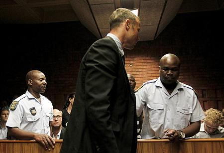 South African 'Blade Runner' Oscar Pistorius (C) is escorted by police during his court appearance in Pretoria February 15, 2013. Pistorius, a double amputee who became one of the biggest names in world athletics, broke down in tears on Friday after he was charged in court with shooting dead his girlfriend, 30-year-old model Reeva Steenkamp, in his Pretoria house. REUTERS/Siphiwe Sibeko