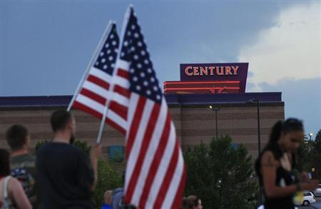 People stand on a hillside behind a memorial for victims behind the theater where a gunman opened fire last Friday on moviegoers in Aurora, Colorado July 22, 2012. REUTERS/Shannon Stapleton