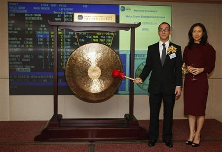 Lawrence Ho (L), co-chairman and chief executive of Melco Crown Entertainment, and his wife Sharen pose with a gong as they attend a ceremony on the dual listing by introduction at the Hong Kong Stock Exchange December 7, 2011. REUTERS/Bobby Yip