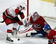 Montreal Canadiens goalie Peter Budaj (30) makes a save against Carolina Hurricanes Jiri Tlusty (19) during first period NHL hockey action in Montreal, February 18, 2013. REUTERS/Christinne Muschi (CANADA - Tags: SPORT ICE HOCKEY) - RTR3DZ0G