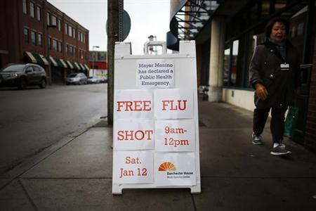 A woman walks past a sign on the street advertising a free flu shot clinic at Dorchester House, a health care clinic, in Boston, Massachusetts January 12, 2013. REUTERS/Brian Snyder/Files