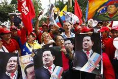 Supporters of Venezuelan President Hugo Chavez take part in a gathering at Plaza Bolivar in Caracas February 18, 2013. REUTERS/Carlos Garcia Rawlins