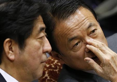 Japan's Prime Minister Shinzo Abe (L) and Finance Minister Taro Aso talk during an upper house budget committee session at the parliament in Tokyo February 18, 2013. Abe said on Monday that the BOJ's monetary easing is aimed at beating deflation, not at manipulating the forex market and weakening the yen, and said correcting excessive yen rises would be an appropriate policy direction. REUTERS/Toru Hanai (JAPAN - Tags: BUSINESS POLITICS)