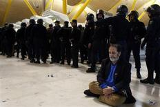 A demonstrator sits on the floor next to Spanish riot police officers at Madrid's Barajas airport February 18, 2013. Striking union workers clashed with police at the airport on Monday on the first day of a week-long strike over more than 3,800 pending job cuts at Spain's flagship airline Iberia. REUTERS/Susana Vera (SPAIN - Tags: CIVIL UNREST TRANSPORT BUSINESS EMPLOYMENT)