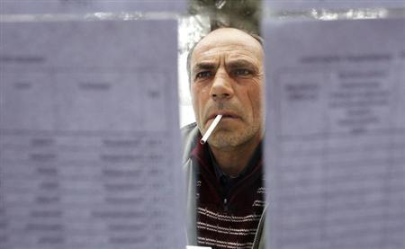 A man looks through a voters' list outside a polling station during Armenia's presidential election in the village of Goght outside Yerevan, February 18, 2013. Armenians voted in a presidential election on Monday that is set to hand incumbent Serzh Sarksyan a new five-year term, but the lack of any serious opposition and an assassination attempt on one of his rivals cast a shadow over the ballot. REUTERS/David Mdzinarishvili (ARMENIA - Tags: POLITICS ELECTIONS)