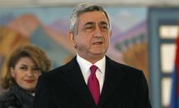 Президент Армении Серж Саргсян и его жена Рита покидают избирательный участок в Ереване 18 февраля 2013 года. Серж Саргсян переизбран на выборах главы государства на новый пятилетний срок, сообщила Центральная избирательная комиссия во вторник. REUTERS/David Mdzinarishvili