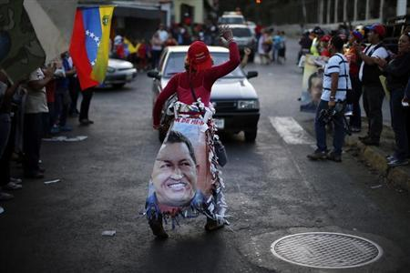 A supporter of Venezuela's President Hugo Chavez cheers outside the military hospital after his surprise return to Caracas February 18, 2013. REUTERS/Jorge Silva