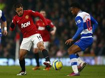 Le Mancunien Javier Hernandez (à gauche) à la lutte avec Garath McCleary de Reading. Manchester United s'est qualifié lundi soir pour les quarts de finale de la Cup en s'imposant à domicile face à Reading sur le score de 2-1. /Photo prise le 18 février 2013/REUTERS/Darren Staples