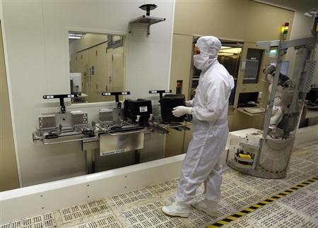 An employee carries a wafer box in a clean room of German semiconductor manufacturer Infineon in Regensburg February 12, 2013. REUTERS/Michael Dalder