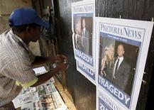 """Un giornalaio appende davanti al tribunale di Pretoria le locandine con la foto di Oscar Pistorius e della fidanzata Reeva Steenkamp, del cui omicidio il """"Blade Runner"""" sudafricano è chiamato a rispondere. REUTERS/Siphiwe Sibeko"""
