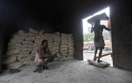 A labourer prepares chewing tobacco inside the wagon of a train as his colleague unloads cement sacks at a yard in Kolkata June 25, 2012. REUTERS/Rupak De Chowdhuri/Files