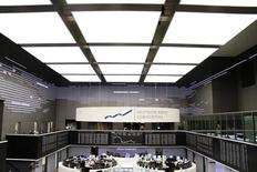 Traders are pictured at their desks in front of the DAX board at the Frankfurt stock exchange February 14, 2013. REUTERS/Pawel Kopczynski (GERMANY - Tags: BUSINESS)