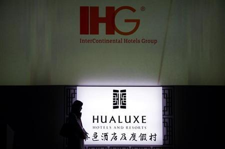 A woman stands near an illuminated sign for InterContinental Hotels Group's (IHG) new hotel brand called Hualuxe Hotels and Resorts, during its official launch inside the Forbidden City in Beijing March 19, 2012. REUTERS/David Gray
