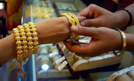 A Hindu married woman wears gold bangles at a jewellery shop on the eve of Teej festival in Allahabad September 1, 2008. REUTERS/Jitendra Prakash/Files