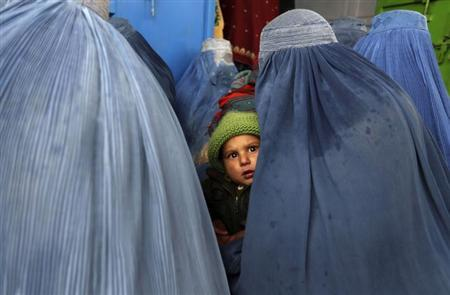 A child and Afghan women, wearing burqas, wait to receive winter relief assistance donated by the Danish Refugee Council (DRC) in the outskirts of Kabul February 3, 2013. REUTERS/Omar Sobhani