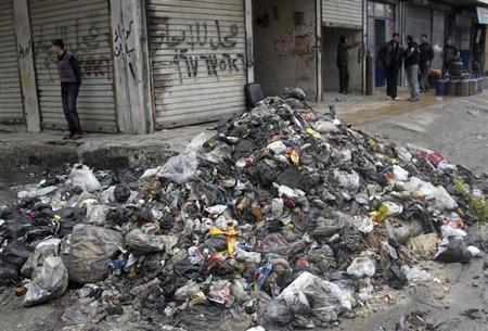 Men stand near garbage filling a street in Aleppo, February 11, 2013. REUTERS/Muzaffar Salman