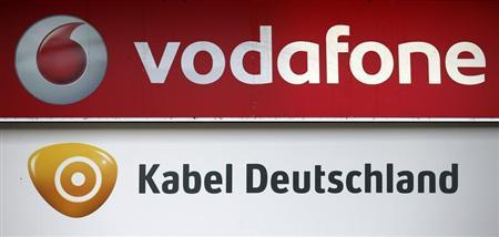 A combination of two photographs shows the logos of Vodafone and Kabel Deutschland at a mobile phone shop in Berlin February 18, 2013. REUTERS/Fabrizio Bensch