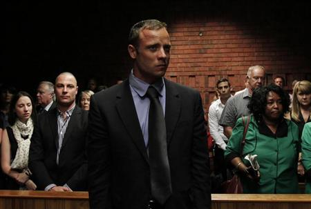 ''Blade Runner'' Oscar Pistorius awaits the start of court proceedings in the Pretoria Magistrates court February 19, 2013. Pistorius, a double amputee who became one of the biggest names in world athletics, was applying for bail after being charged in court with shooting dead his girlfriend, 30-year-old model Reeva Steenkamp, in his Pretoria house. REUTERS/Siphiwe Sibeko