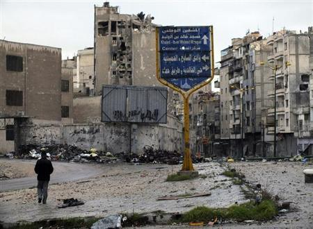 A man walks past a signpost in a neighbourhood filled with damaged buildings and debris in the Khaldiyeh area of Homs February 19, 2013. REUTERS/Yazan Homsy