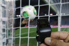 Представитель ФИФА держит браслет, используемый в системе для определения взятия ворот GoalRef, во время демонстрационного показа в Йокогаме 5 декабря 2012 года. Управляющий орган мирового футбола - ФИФА - подтвердил во вторник, что на чемпионате мира 2014 года будут использоваться автоматические системы определения взятия ворот, и пригласил разработчиков подобных технологий к участию в тендере. REUTERS/Toru Hanai