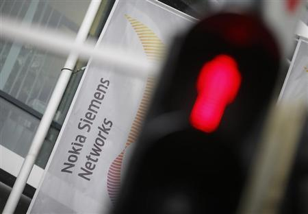 A red traffic light is pictured next to the company logo of Mobile network equipment maker Nokia Siemens Networks (NSN), in Munich November 29, 2012. REUTERS/Michael Dalder