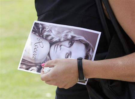 A mourner leaves, holding a picture of model Reeva Steenkamp, after her memorial service at the Victoria Park Crematorium in Port Elizabeth February 19, 2013. Steenkamp's boyfriend Olympic and Paralympic athlete Oscar Pistorius has been charged with her murder. REUTERS/Rogan Ward