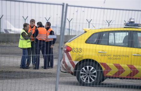 Airport security guards and officials stand near an entrance to the tarmac at Zaventem international airport near Brussels February 19, 2013. REUTERS/Eric Vidal
