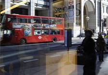 Las primas para los directivos de entidades bancarias podrían tener como límite sus salarios fijos anuales si las autoridades y los estados miembros de la Unión Europea alcanzan un acuerdo en el marco de unas importantes negociaciones que se llevan a cabo el martes. Imagen de unas personas y un autobús refejados en el ventanal de una sucursal de Royal Bank of Scotland en Londres el 27 de enero. REUTERS/Paul Hackett