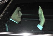 Il leader del Pdl ed ex presidente del Consiglio Silvio Berlusconi saluta dall'auto. REUTERS/Paolo Bona