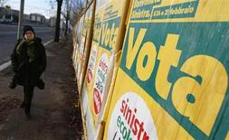 Женщина проходит мимо предвыборных плакатов в Риме 24 января 2013 года. За пять дней до общенациональных выборов почти треть итальянцев не определились с предпочтениями в отношении кандидатов или не собираются голосовать вообще. REUTERS/Tony Gentile