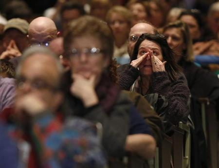 People react as they sit and watch families of Sandy Hook shooting victims testify at a public hearing on gun control at Newtown High School in Newtown, Connecticut January 30, 2013. REUTERS/Carlo Allegri
