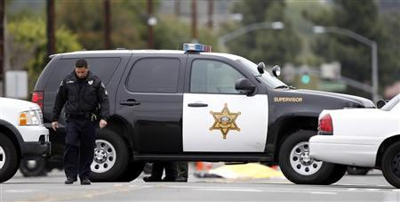 A man, believed to be the shooter, lies dead in the street near an Orange County Sheriff's vehicle in Villa Park, California, February 19, 2013. REUTERS/Alex Gallardo