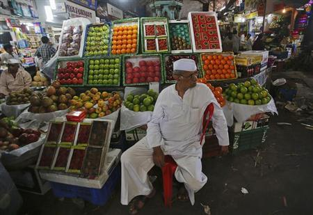 A fruit seller waits for customers at his stall at a wholesale market in Mumbai February 14, 2013. REUTERS/Vivek Prakash
