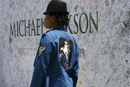 Latasha Dobson, a fan of deceased pop star Michael Jackson, stand in front of a large poster outside Staples Center in Los Angeles July 6, 2009. REUTERS/Mario Anzuoni/Files