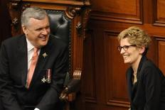 Kathleen Wynne (R) laughs with Lieutenant Governor of Ontario David Onley after being sworn in as the Premier of Ontario in the Legislative Chamber at Queen's Park in Toronto February 11, 2013. REUTERS/Jon Blacker