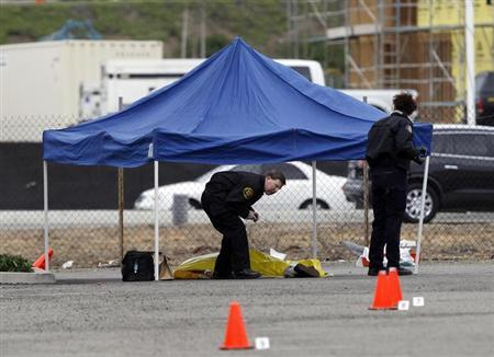 Police authorities walk near the body of a man in the parking lot of a computer store, after he was shot while returning to his vehicle, in Tustin, California, February 19, 2013. REUTERS/Alex Gallardo