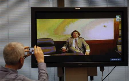 Former cyclist Tyler Hamilton of the U.S. is seen on a TV screen as he testifies through video conference from the Spanish Embassy in Washington, during the high-profile Operacion Puerto doping trial in Madrid February 19, 2013. REUTERS/Sergio Perez