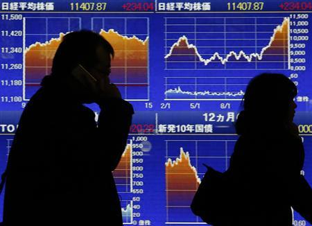 Passersby walk past an electronic board showing Japan's Nikkei movements outside a brokerage in Tokyo February 18, 2013. REUTERS/Yuya Shino