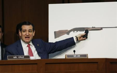 U.S. Senator Ted Cruz, (R-TX), holds a plastic hand grip in front of a picture of a hunting rifle as he questions NRA CEO Wayne LaPierre (not in photo) about the effect of proposed gun control legislation during a hearing held by the Senate Judiciary committee on Capitol Hill in Washington January 30, 2013.REUTERS/Kevin Lamarque