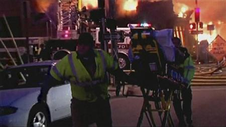 A still image taken from a KHSB-TV video footage shows emergency workers pulling a person on a gurney near the scene of the fire at Kansas City, Missouri February 19, 2013. REUTERS/KHSB-TV