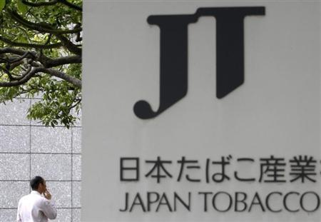 A man smokes a cigarette behind a logo of Japan Tobacco Inc (JT) outside the company's headquarters building in Tokyo, in this file photo taken May 31, 2012. REUTERS/Yuriko Nakao/Files