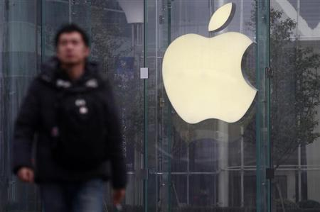 A man walks in front of a company logo outside an Apple store in downtown Shanghai January 24, 2013. REUTERS/Aly Song/Files