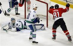 Chicago Blackhawks' Marian Hossa (R) celebrates his goal on Vancouver Canucks' Cory Schneider (L) as Canucks' Henrik Sedin looks on during the second period of their NHL hockey game in Chicago, Illinois, February 19, 2013. REUTERS/Jim Young