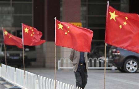 A man walks past Chinese national flags tied to iron fences at Chaoyang Hospital, where blind activist Chen Guangcheng was reported to be staying at, in Beijing May 2, 2012. REUTERS/Jason Lee/Files