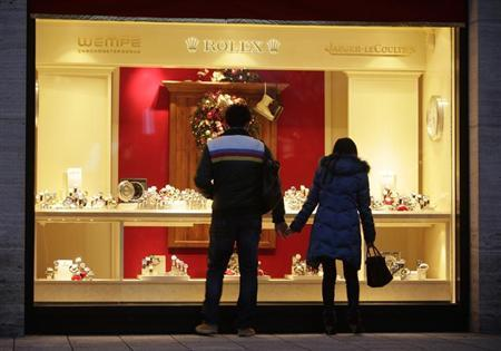 A couple looks into a shop window of a jeweller in the city centre of Frankfurt December 18, 2012. With record low interest rates providing little incentive to open a bank account, canny Germans are choosing a more glamorous place to put their money this Christmas - jewellery. Picture taken December 18, 2012. TO GO WITH STORY GERMANY-SHOPPING/JEWELLERY REUTERS/Lisi Niesner (GERMANY - Tags: BUSINESS SOCIETY)