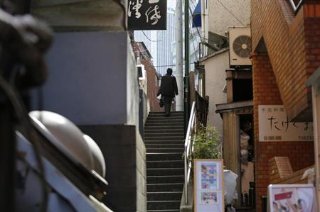 A man walks up a flight of stairs in Tokyo February 20, 2013. Tight-fisted companies in Japan may prove the biggest obstacle in Prime Minister Shinzo Abe's plan to push the sluggish economy into higher gear as they intend to keep a firm lid on wage levels, a Reuters survey shows. Abe has directly appealed to Japan's biggest business lobbies to raise salaries and break more than two decades of falling average wage levels, aware of how critical rising incomes are if Japan is finally to emerge from years of deflation. To match Exclusive JAPAN-ECONOMY/WAGES REUTERS/Toru Hanai (JAPAN - Tags: POLITICS BUSINESS EMPLOYMENT)