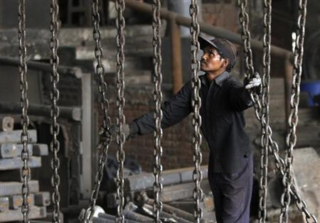 A worker unloads steel bars from a trolley at an iron and steel factory on the outskirts of Jammu February 1, 2013. REUTERS/Mukesh Gupta/Files