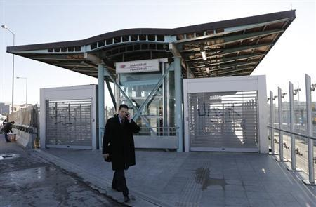 A man walks in front of a closed entrance of a suburban station during a 24-hour strike in Chalandri suburb north of Athens February 20, 2013. Greek workers walked off the job on Wednesday in a nationwide protest against wage cuts and high taxes, keeping ferries docked in ports, shutting state schools and leaving hospitals working with emergency staff. REUTERS/John Kolesidis (GREECE - Tags: POLITICS BUSINESS EMPLOYMENT)