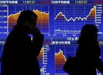 Tokyo, passanti davanti a un tabellone elettronico con le performance dell'indice di borsa Nikkei, lo scorso 18 febbraio. REUTERS/Yuya Shino
